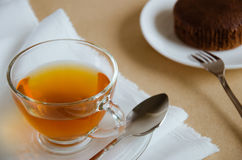 Glass Cup of Tea and Chocolate Cake for Tea Break. Glass cup of hot tea and chocolate cake for tea break time Royalty Free Stock Photography