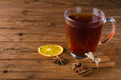 Glass cup of tea, cinnamon and anise on a wooden background. Royalty Free Stock Image