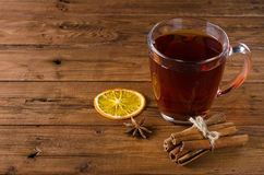 Glass cup of tea, cinnamon and anise on a wooden background. Royalty Free Stock Photo