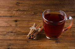 Glass cup of tea and cinnamon on a wooden background. Stock Photo