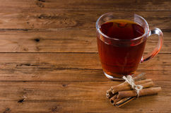Glass cup of tea and cinnamon on a wooden background. Royalty Free Stock Photo