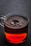 Glass cup of tea  with falling drop Stock Photography