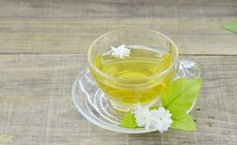 Glass cup with tea and fresh jasmine flowers on wooden table royalty free stock photos