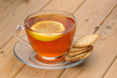 Glass cup with tea and a lemon on a glass saucer and cookies Royalty Free Stock Photo