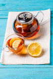 Glass cup of tea with lemon and glass teapot. Stock Image