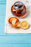 Glass cup of tea with lemon and glass teapot. Royalty Free Stock Photos