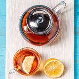Glass cup of tea with lemon and glass teapot. Royalty Free Stock Photo