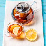 Glass cup of tea with lemon and glass teapot. Royalty Free Stock Image