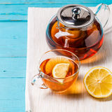 Glass cup of tea with lemon and glass teapot. Stock Photos