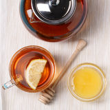 Glass cup of tea with lemon, glass teapot and honey. Stock Image