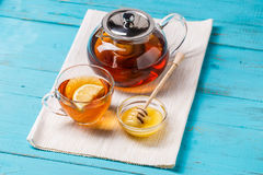 Glass cup of tea with lemon, glass teapot and honey. Stock Photos