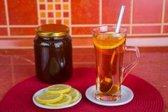 Glass cup of tea with lemon and honey. Stock Photo