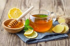 A glass cup of tea with lemon, mint, ginger and honey royalty free stock photography