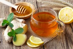 A glass cup of tea with lemon, mint, ginger and honey. On wooden rustic table royalty free stock photo