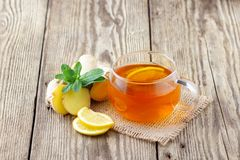 A glass cup of tea with lemon, mint and ginger. On wooden rustic table royalty free stock photos