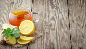 A glass cup of tea with lemon, mint and ginger. On wooden rustic table royalty free stock photo
