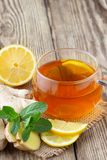 A glass cup of tea with lemon, mint and ginger. On wooden rustic table stock photos