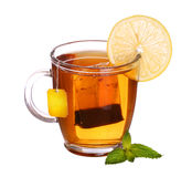 Glass cup of tea with lemon and mint on white. Glass cup of tea with lemon and mint isolated on white background Royalty Free Stock Images