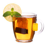 Glass cup of tea with lemon and mint on white. Glass cup of tea with lemon and mint isolated on white background Stock Photography