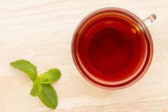 Glass cup of tea with mint on the bright wooden table Royalty Free Stock Image