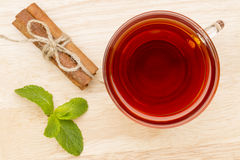 Glass cup of tea with mint and cinnamon stick on the wooden table Royalty Free Stock Photos