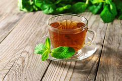 Glass cup of tea with a mint leaf on a saucer on a wooden table closeup Royalty Free Stock Images