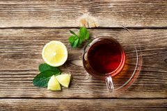 Glass cup with tea, mint and lemon royalty free stock photos
