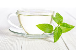 Glass cup of tea with mint on the wooden table Royalty Free Stock Photos