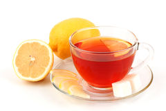 Glass cup of tea near several lemons. Stock Photography