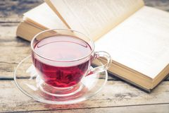 Glass cup of tea with old book on wood background Royalty Free Stock Image