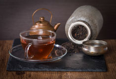 Glass cup of tea, old  jar and a vintage teapot Royalty Free Stock Photo