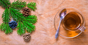 Glass Cup of tea on an old rustic table with pine branch.New yea Stock Photos