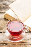 Glass Cup of tea with open book on old wooden table Stock Images