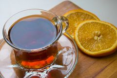 Glass cup of tea with orange slices on a wooden tray stock images