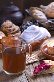 Glass cup of tea and rolls with poppy in a wooden basket glass cup of tea and rolls with poppy stock image