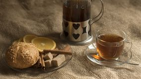 Glass cup of tea and saucer of bread braun sugar and cinnamon rolls on a linen background royalty free stock image