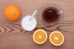 Glass cup of tea with sugar and orange on the table Royalty Free Stock Photos