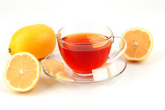 Glass cup of tea surrounded by lemons. Royalty Free Stock Images