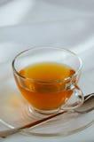 Glass Cup of Tea for Tea Break. Glass cup of tea on white fabric for tea break Stock Photo