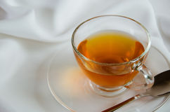Glass Cup of Tea for Tea Break. Glass cup of tea on white fabric for tea break Royalty Free Stock Image