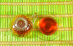 Glass cup of tea and teapot on bamboo background Stock Images