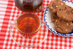 Glass cup of tea, teapot and cookies Stock Images