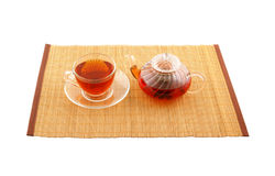 Glass cup of tea and teapot on placemate Royalty Free Stock Photos