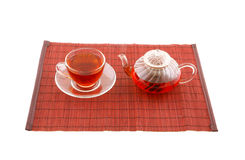 Glass cup of tea and teapot on placemate Stock Photo