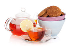 Glass cup and teapot of black tea with lemon and cookies Royalty Free Stock Photography
