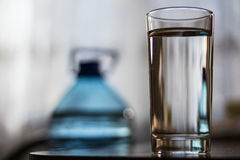 Glass Cup with water and a plastic bottle. On the table is a glass beaker with water. In the blurred background, you can see a large blue plastic water bottle Stock Image
