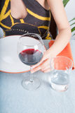 Glass cup of wine in woman hand on blue tablecloth Stock Photo