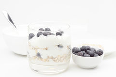 Glass Cup with yogurt, oatmeal and blueberries, next to the dish Stock Photo