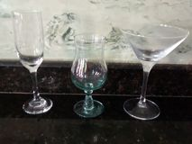 GLASS CUPS OF DIFFERENT SIZES. BETWEEN THEM WE HAVE: CUP FOR MARTINI. CUP FOR WHITE WINE AND CUP FOR COCKTAILS. MATERIALS OF RESTAURANTS AND HOTELS royalty free stock image