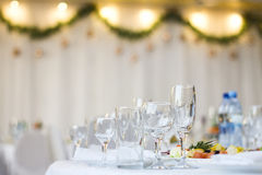 Glass cups and glasses on the table in a restaurant with a New Year`s interior. Royalty Free Stock Photos